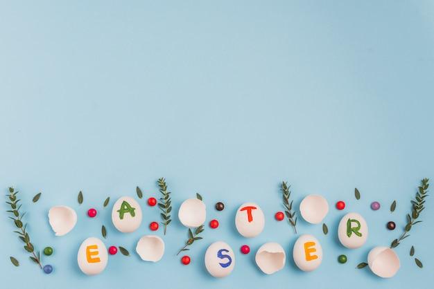 Inscrição de páscoa em ovos com galhos de plantas e doces