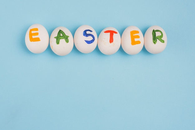 Inscrição de páscoa em ovos na mesa azul
