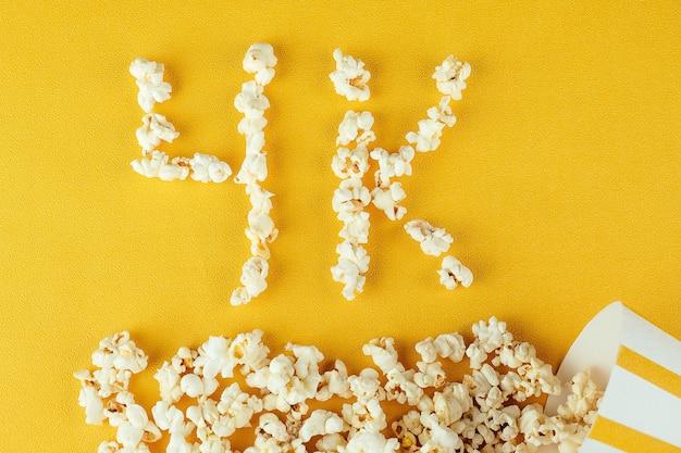 Inscrição de pipoca 4k. o conceito de filmes caseiros e filmes no cinema. qualidade de cinema. pipoca de grãos de milho.