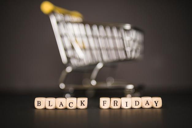 Inscrição de sexta-feira negra em cubos com carrinho de supermercado