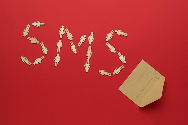 Inscrição de sms feita de homens de madeira e um envelope de papel postal aberto sobre um fundo vermelho. o conceito de comunicação entre pessoas.