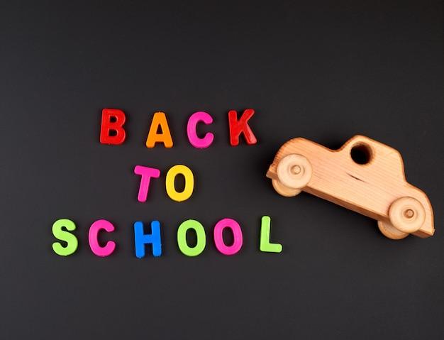 Inscrição de volta à escola de letras plásticas coloridas e carrinho de bebê de madeira no quadro de giz preto