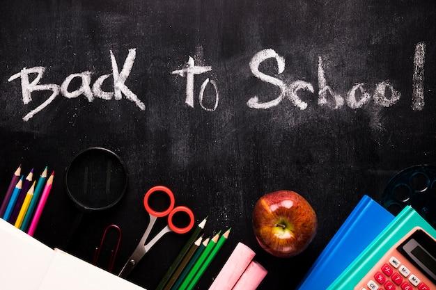 Inscrição de volta à escola e papelaria no quadro-negro