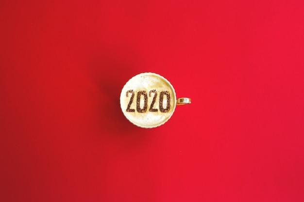 Inscrição do conceito de 2020 anos em uma xícara de cappuccino no vermelho.