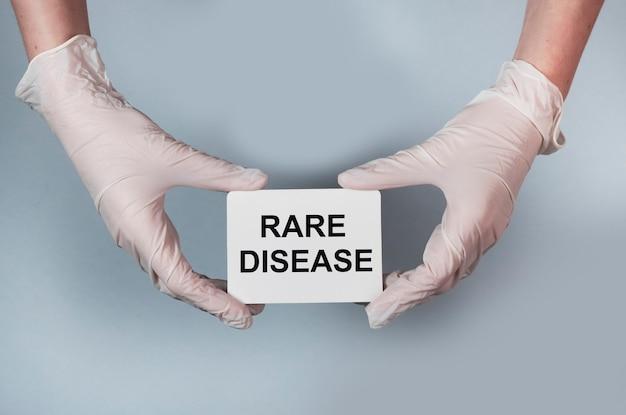 Inscrição do conceito de doença rara em papel nas mãos com luvas brancas