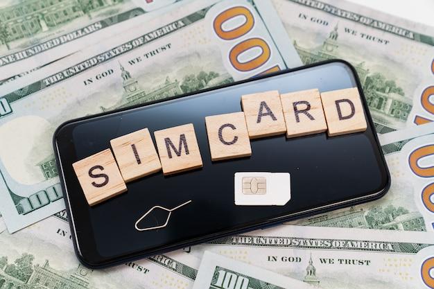 Inscrição em cubos e cartão sim e no smartphone e notas de dólar