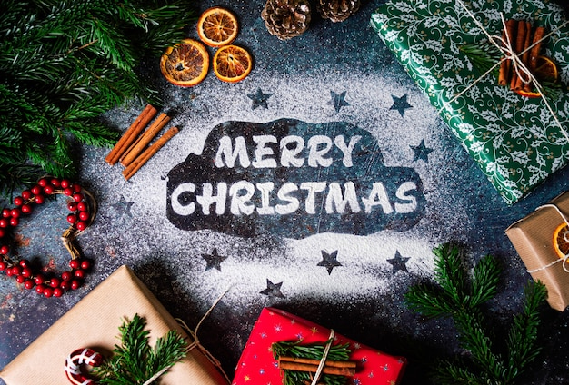 Inscrição feita à mão feliz natal de farinha em fundo escuro com caixas de presente em papel de embrulho colorido, laranjas secas, ramos de pinheiro