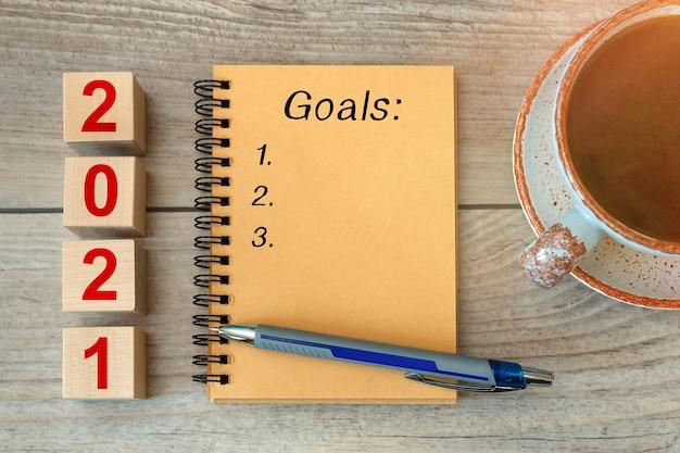 Inscrição goals em um caderno e cubos de madeira uma xícara com café