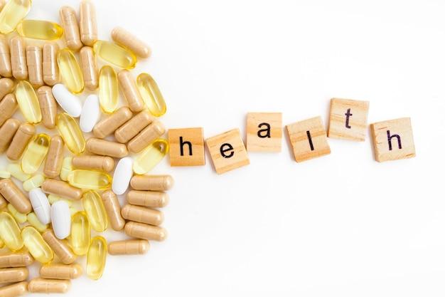 Inscrição health em cubos de madeira em um fundo branco de diferentes pílulas