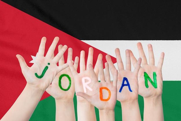Inscrição jordan nas mãos das crianças contra uma bandeira agitando do jordão