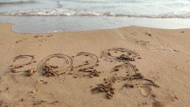 Inscrição manuscrita 2020 e 2021 na areia da praia do mar. fundo