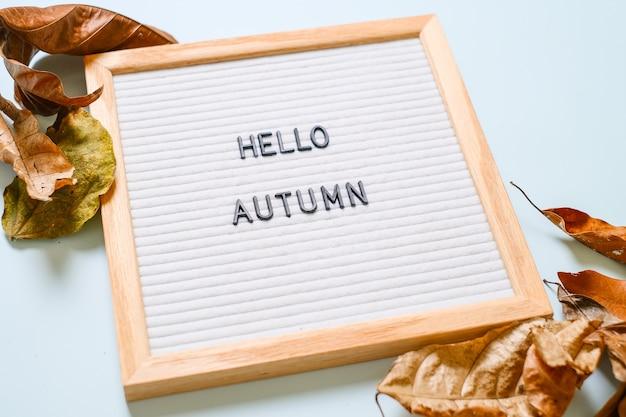 Inscrição olá outubro no quadro do correio branco, com folhas secas sobre fundo azul claro. conceito de outono