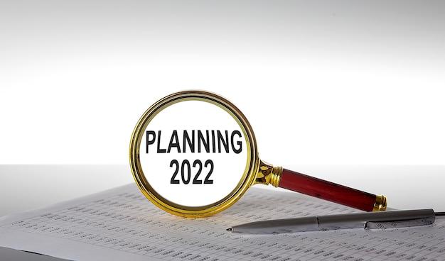 Inscrição planejando 2022 na lupa com gráfico e caneta