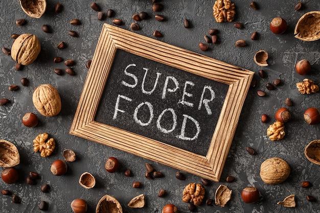 Inscrição super food, várias nozes na mesa de pedra