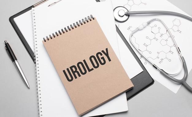 Inscrição urologia. vista superior da mesa com estetoscópio, caneta e documentos médicos.