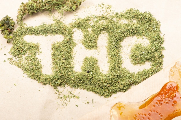 Inscrição word thc com botões de cannabis verdes esmagados e cera dourada com alto thc.