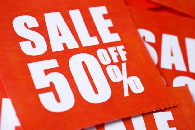Inscrições à venda em percentagens impressas em papel vermelho.
