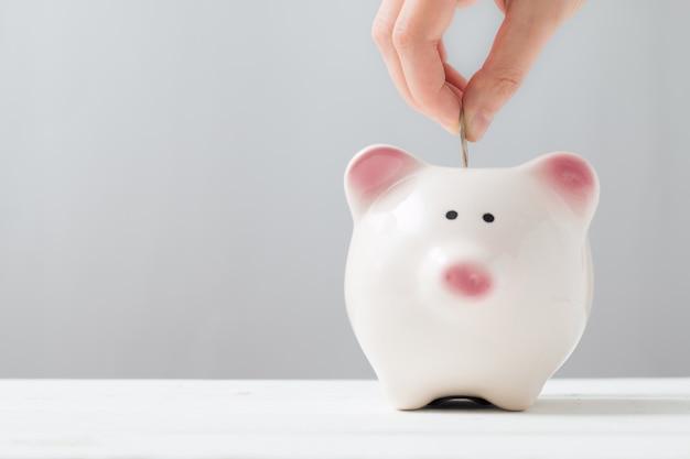 Inserindo uma moeda em um cofrinho. estilo minimalista. conceito de poupança de dinheiro.