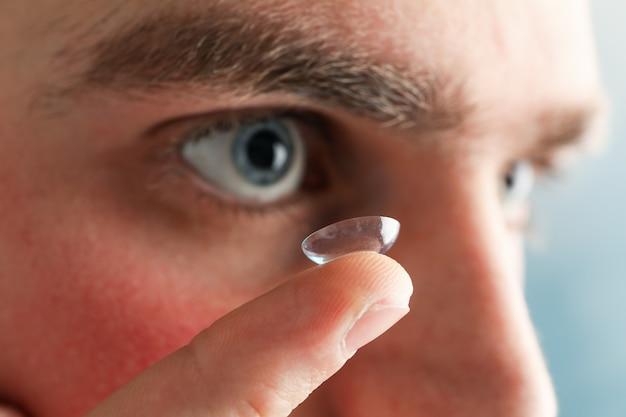 Inserir uma lente de contato corretiva. homem de olhos azuis
