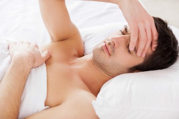 Insônia. homem jovem e bonito sem camisa segurando a mão no cabelo e mantendo os olhos fechados enquanto estava deitado na cama