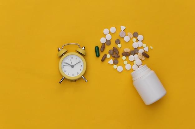 Insônia. mini despertador e comprimidos de frasco em fundo amarelo.