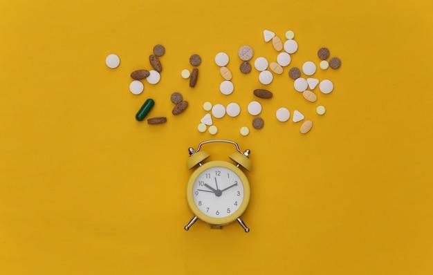 Insônia. mini despertador e comprimidos em fundo amarelo.