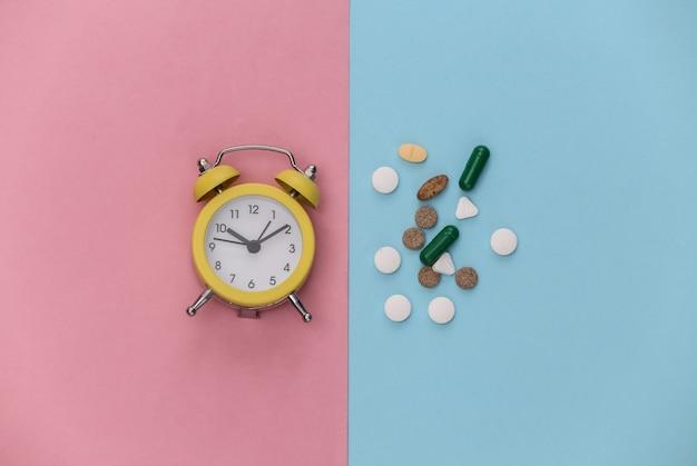 Insônia. mini despertador e pílulas em fundo rosa azul pastel.