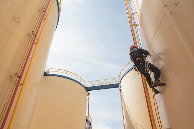 Inspeção de acesso por corda de trabalhador masculino da indústria de tanques brancos de armazenamento de espessura