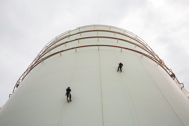 Inspeção de segurança de acesso de escada de corda de placa de escudo de tanque de altura do trabalhador masculino de dois trabalhadores de propano de gás de tanque de armazenamento de espessura.