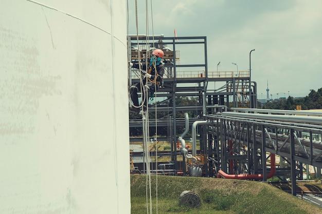 Inspeção de segurança de altura de acesso por corda de trabalhador masculino da indústria de tanques de óleo e gás de armazenamento de espessura