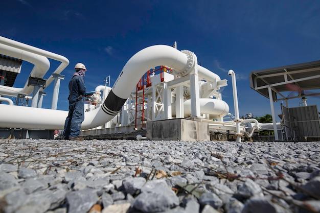 Inspeção de trabalhador masculino em tubos longos de aço e cotovelo de tubo na fábrica de óleo da estação durante a válvula da refinaria do registro de verificação visual da indústria de petróleo e gás
