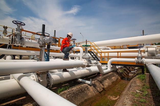 Inspeção de trabalhador masculino na válvula do registro de verificação visual da indústria de óleo e gás do oleoduto