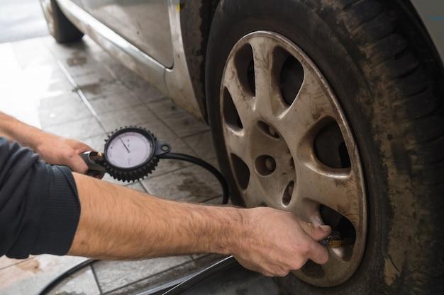 Inspeção do carro na oficina, verificação da pressão das rodas com a pistola de ar, inspeção técnica anual do veículo