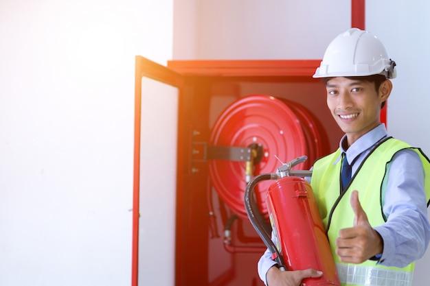 Inspeção do engenheiro extintor de incêndio e mangueira de incêndio.
