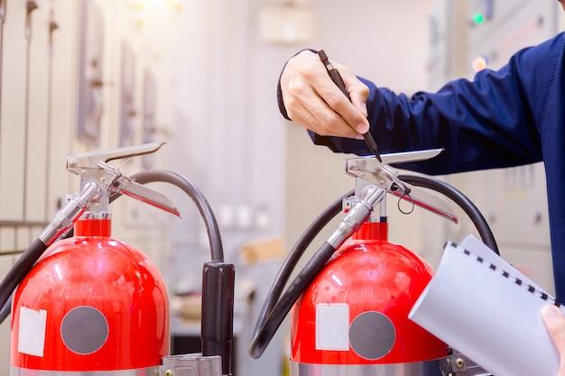 Inspeção do engenheiro extintor de incêndio na sala de controle.