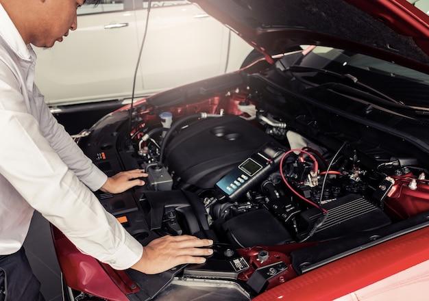 Inspeção do homem que prende o voltímetro do verificador da capacidade da bateria.