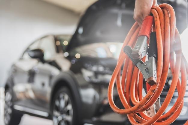 Inspeção do homem segurando os cabos de ligação em ponte para o carregador manutenção de serviços de bateria de carros