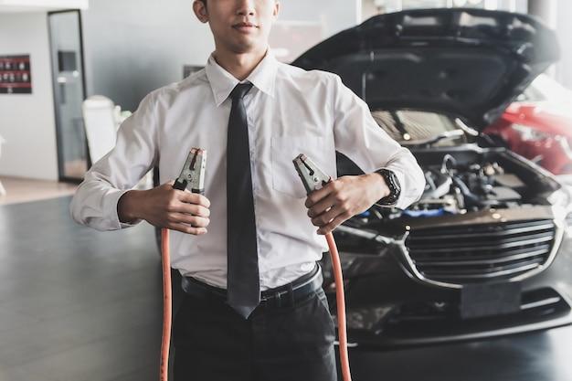 Inspeção do homem segurando os cabos de ligação em ponte para o carregador serviço de manutenção da bateria do carro