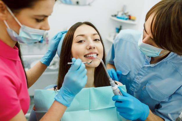 Inspeção dos dentes da mulher com a ajuda de um espelho.