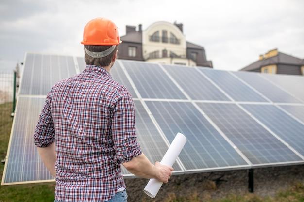 Inspeção. vista traseira do homem com capacete e camisa xadrez com desenho na mão olhando para o painel solar na zona rural