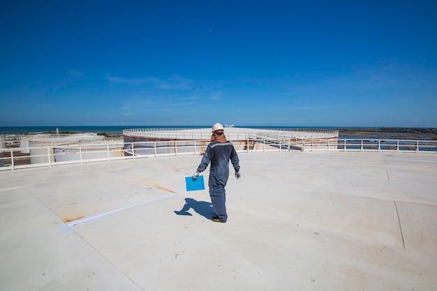 Inspecção de trabalhador masculino visual telhado tanque de armazenamento de óleo fundo cidade e céu azul