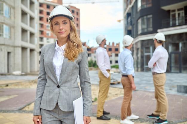 Inspetor adorável e seus colegas inspecionando a área de construção