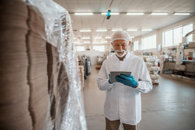 Inspetor adulto sênior caucasiano sorridente, vestido com uniforme branco, usando tablet para avaliação de qualidade de alimentos na fábrica de alimentos.
