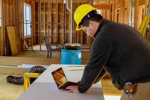 Inspetor com capacete amarelo e fita métrica e tablet no local de trabalho