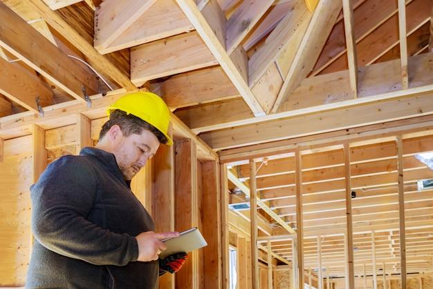 Inspetor da casa da construção que inspeciona a casa para ver se o trabalho foi feito corretamente