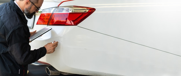 Inspetor de acidentes inspecione o carro danificado causado por acidente de carro na estrada. agente de seguros de automóveis examinando o carro branco pelo tablet digital na garagem.
