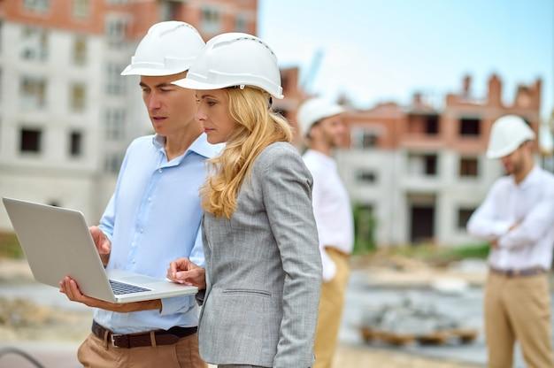 Inspetor de construção e um trabalhador olhando para o monitor do computador