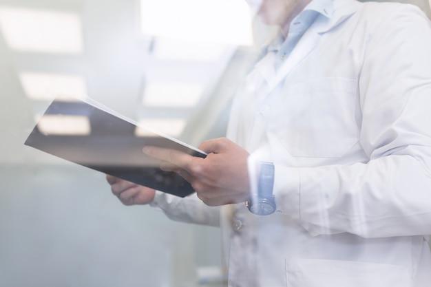 Inspetor de qualidade, usando vestido médico branco, inspecionando um laboratório