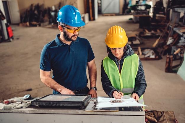 Inspetor de segurança no local de trabalho, escrevendo um relatório na fábrica industrial