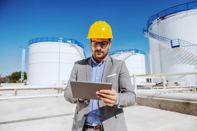 Inspetor dedicado atraente de terno e com o capacete na cabeça em pé ao ar livre na refinaria e usando o tablet.